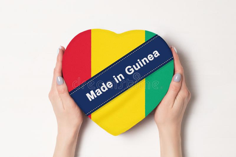 Inscription Made in Guinea the flag of Guinea. Female hands holding a heart shaped box. White background stock photo