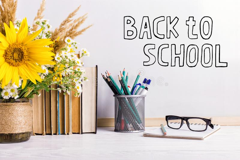 The inscription marker on a white board, Back to School. A table with books, a bouquet of flowers, glasses and attributes for stock photo