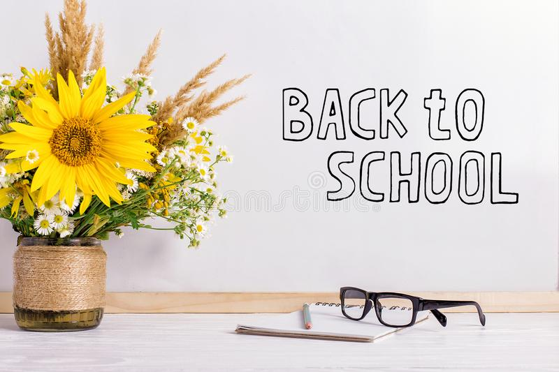 The inscription marker on a white board, Back to School. A table with a bouquet of flowers, glasses and attributes for writing. The inscription marker on white stock photos