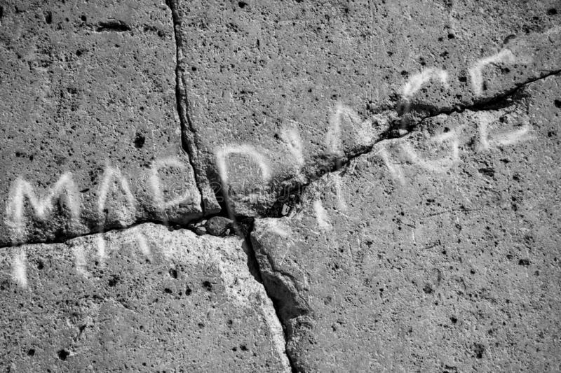 Dark gray stone wall  , inscription marriage broke up. Inscription marriage on a cracked stone, gray color, symbolizing the difficulties in marriage and divorce stock images