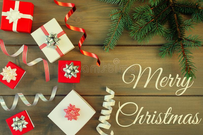 The inscription from Merry Christmas on the background of brown wood. Christmas composition of gift boxes with bows. Decorative ribbons and Christmas tree royalty free stock images
