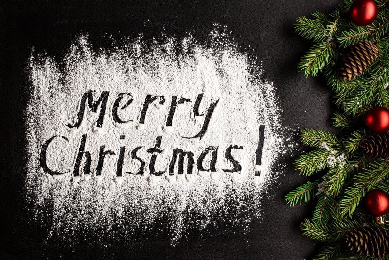 Inscription MERRY CHRISTMAS on powdered sugar background stock photos