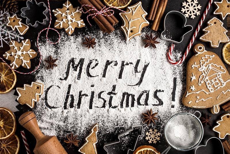 Inscription MERRY CHRISTMAS on powdered sugar background stock photo