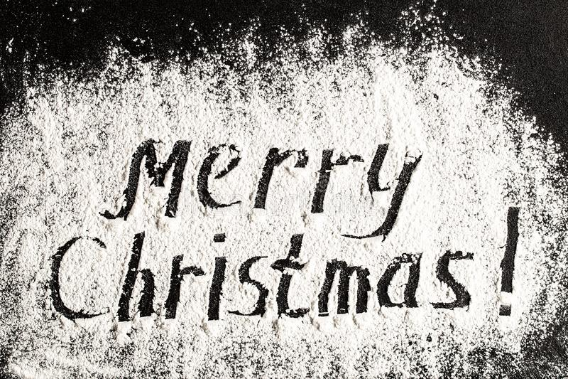 Inscription MERRY CHRISTMAS on powdered sugar background. royalty free stock images