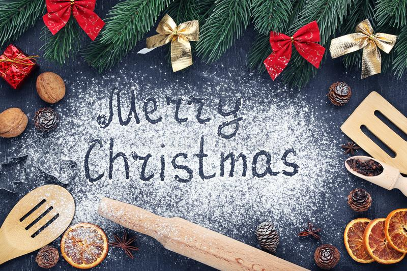 Inscription Merry Christmas on wheat flour background with fir-tree branches and wooden spoons royalty free stock photo