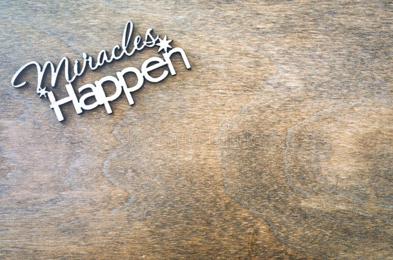 Inscription miracles happen on a wooden background. Concept of inspiration and hope. royalty free stock image