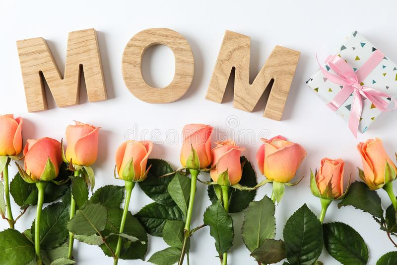 Inscription Mom with pink roses and gift on two tone background. Top view royalty free stock photo