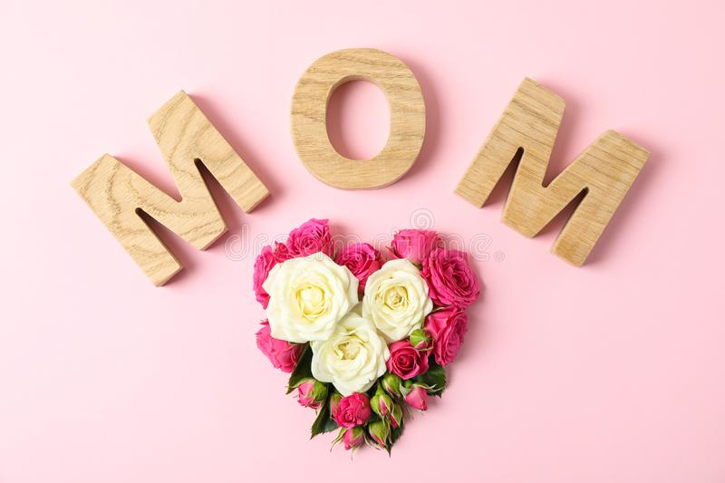 Inscription Mom with roses in shape of heart on color background. Top view royalty free stock photos