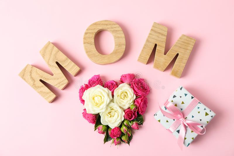 Inscription Mom with roses in shape of heart and gift on color background. Top view stock images