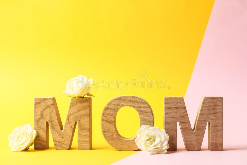Inscription mom with roses on two tone background. Space for text stock images