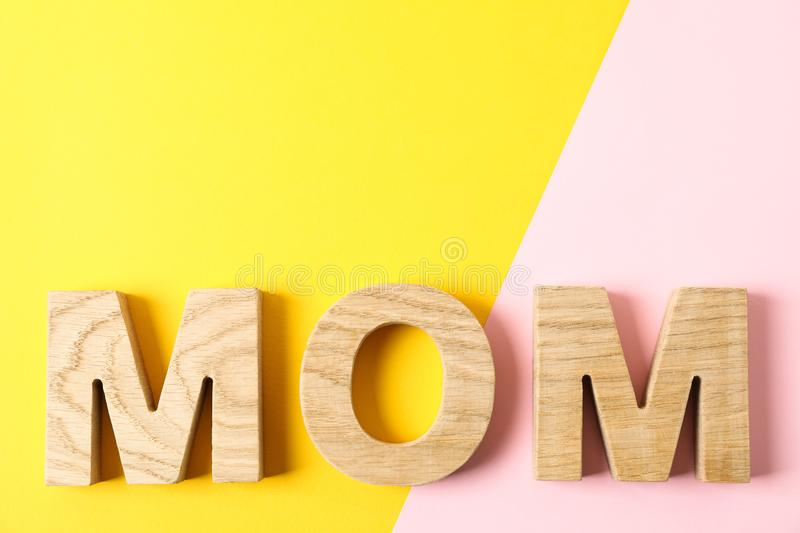 Inscription mom with space for text on two tone background. Top view stock photography