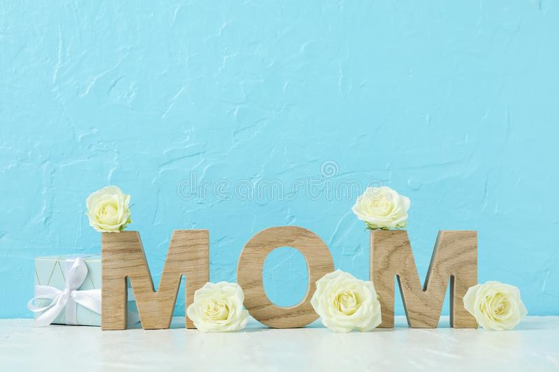 Inscription Mom with white roses on pink table against color background stock images