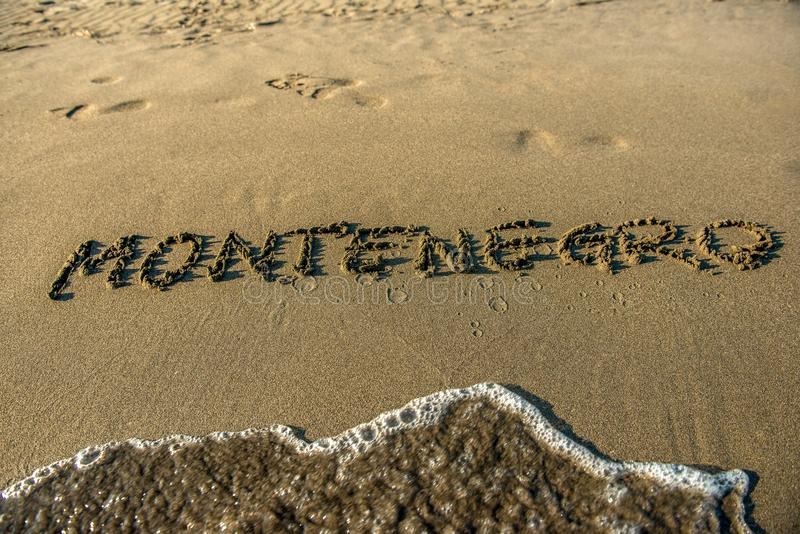 Inscription `Montenegro` written with a finger on the wet sand on the beach stock photos