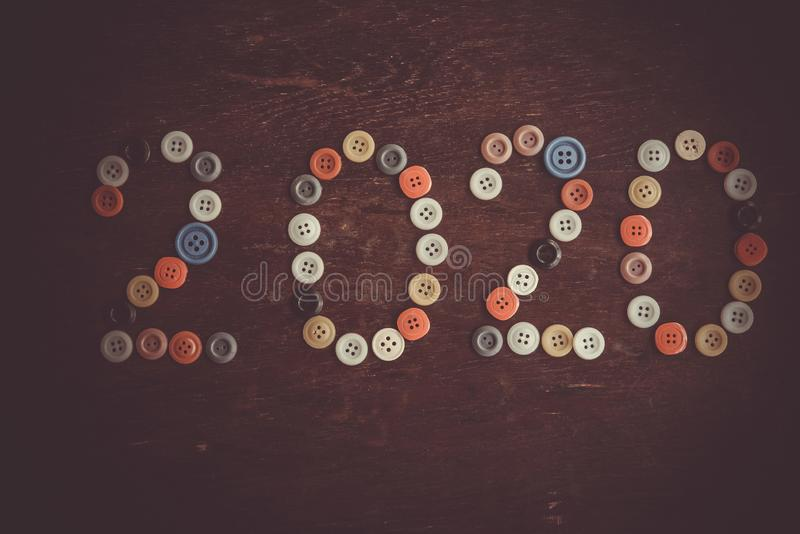 Inscription 2020 from multi colored buttons on dark old wooden background. Happy New Year stock image