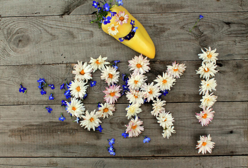 Inscription `OK!` from flowers on wooden background with pepper in form of emoticon. Optimistic inscription `OK!` from flowers on old unpainted wooden stock photo