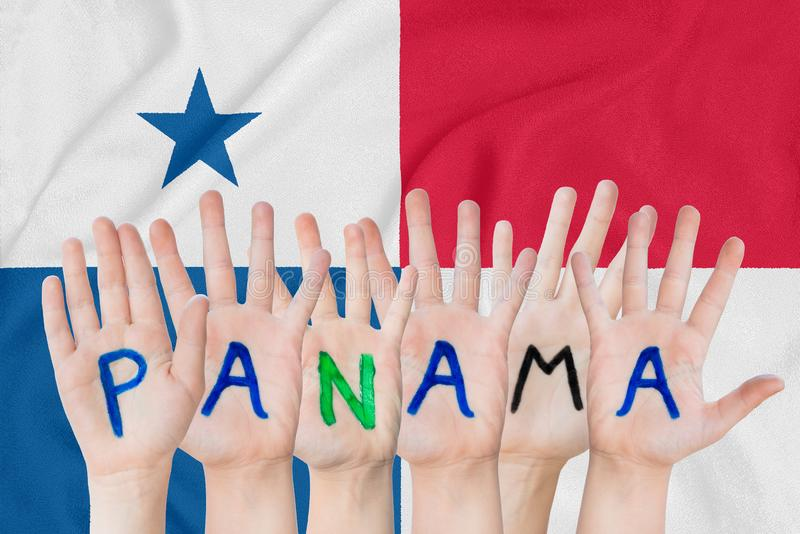 Inscription Panama on the children`s hands against the background of a waving flag of the Panama royalty free stock images