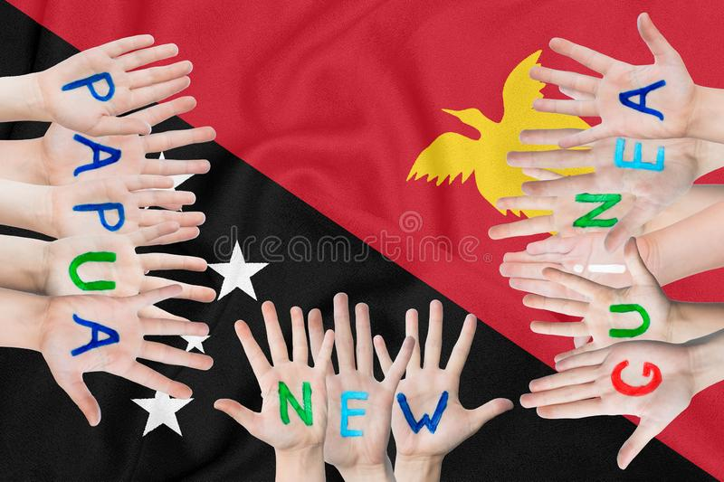 Inscription Papua New Guinea on the children`s hands against the background of a waving flag of the Papua New Guinea.  stock images