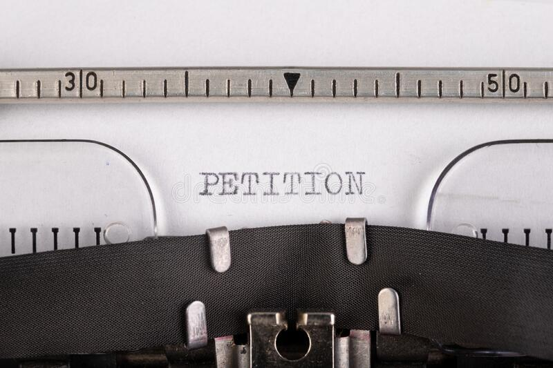 """The inscription """"petition"""" on a white sheet of paper in an old typewriter. The old method of printing text royalty free stock images"""