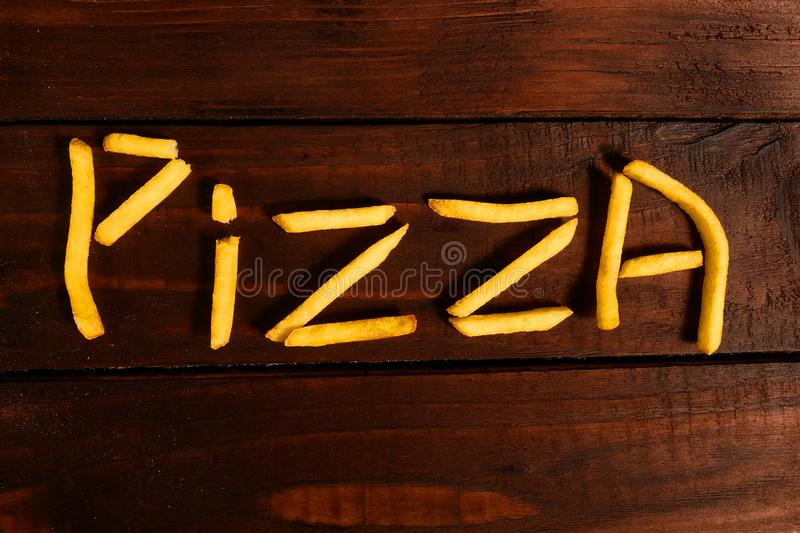 The inscription pizza made of French fries royalty free stock photography