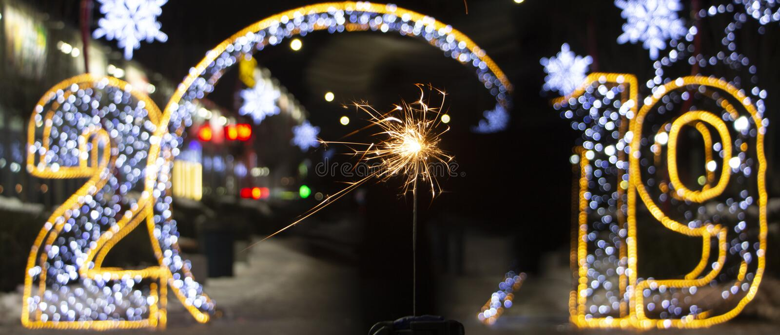 The inscription 2019 in Rasfokus, sparkler in the foreground, the concept of the new year royalty free stock photography
