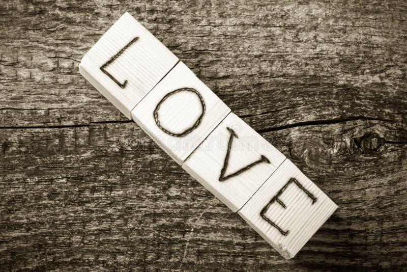 Inscription romantique des lettres sur les cubes en bois légers sur un vieux g photo libre de droits