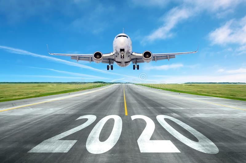 The inscription on the runway 2020 surface of the airport runway with take off aircraft. Concept of travel in the new year,. Holidays stock images