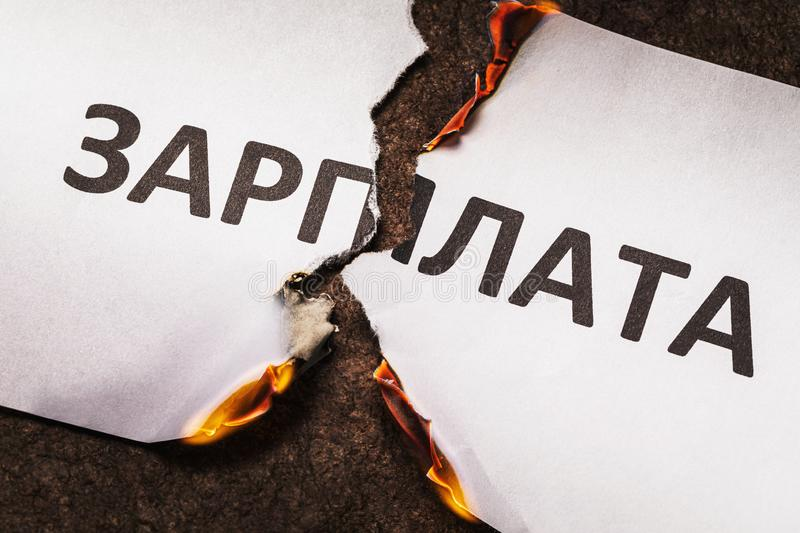 The inscription in Russian is salary. A burning sheet of paper is torn in half stock photography