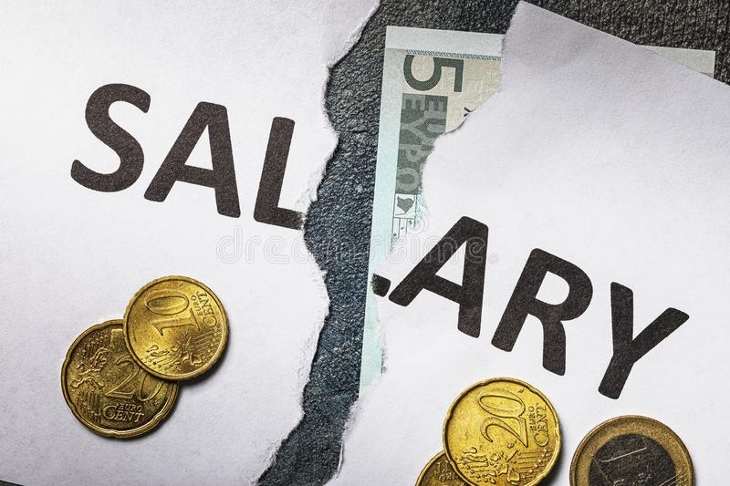 The inscription salary is torn in half, and next to it are euro coins. Concept on the financial crisis royalty free stock photo