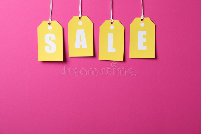 Inscription Sale on price tags on pink background. Black Friday. Concept stock images