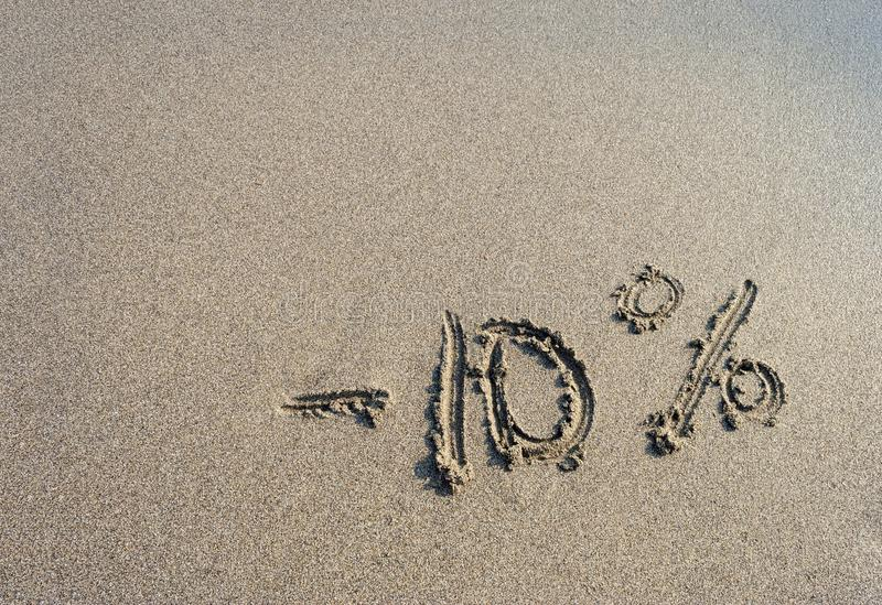 Inscription on the sand minus ten percent, 10 % royalty free stock photography