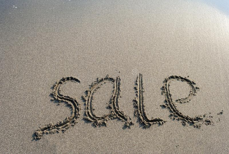 Inscription on the sand sale, letters on the sand on the beach royalty free stock photo