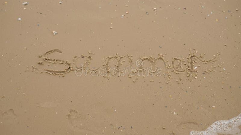 Inscription on the sand the word summer on the sea beach.  stock photo