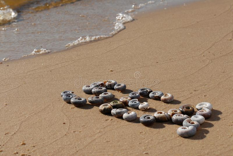 The inscription `Sea` is  written by small sea shellson the yellow sand. The inscription `Sea`, written on a sunny summer morning on the yellow sand of the sea stock image