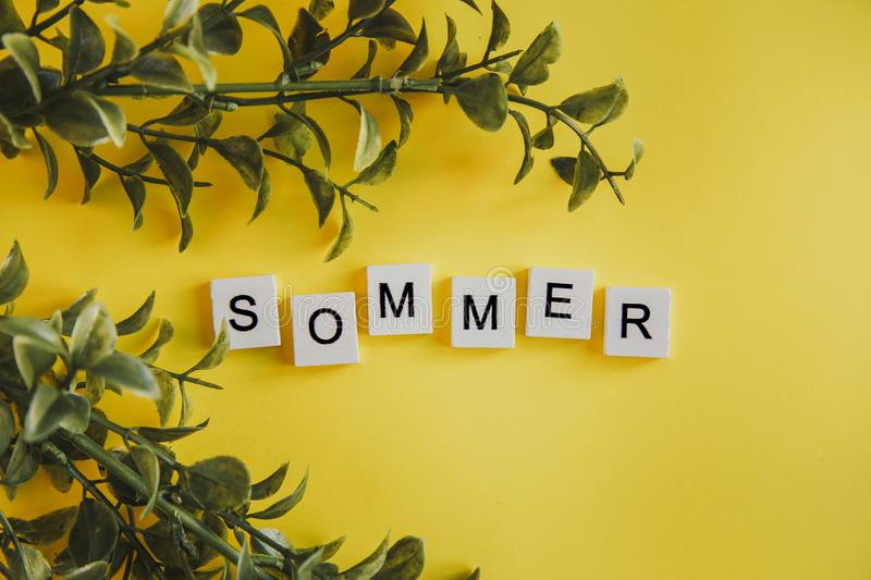 The inscription sommer in german on the letters of the keyboard on a yellow background with flowers. The inscription sommer in german on the letters of the stock images