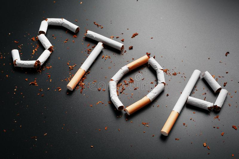 The inscription STOP from cigarettes on a black background. Stop smoking. The concept of smoking kills. Motivation inscription to. Quit smoking, unhealthy habit stock image