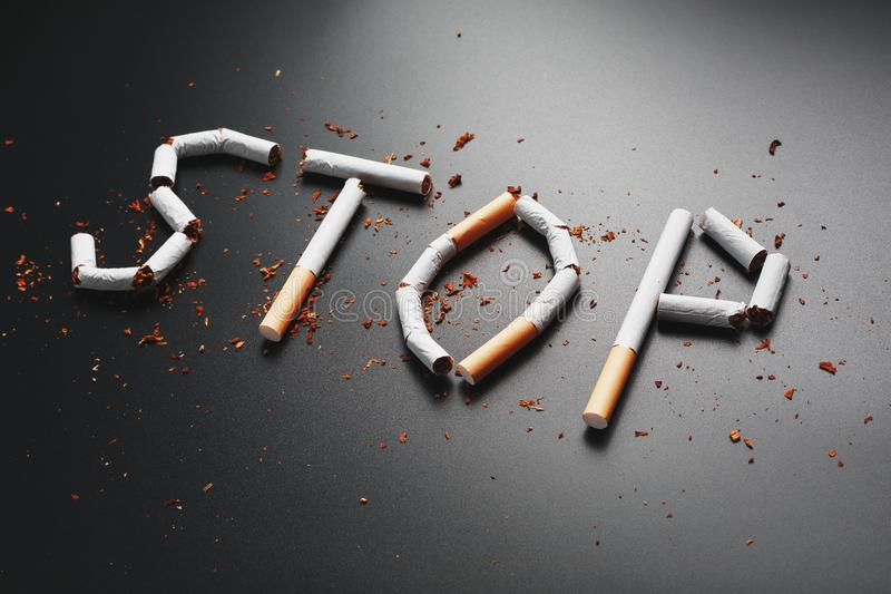The inscription STOP from cigarettes on a black background. Stop smoking. The concept of smoking kills. Motivation inscription to. Quit smoking, unhealthy habit stock photo