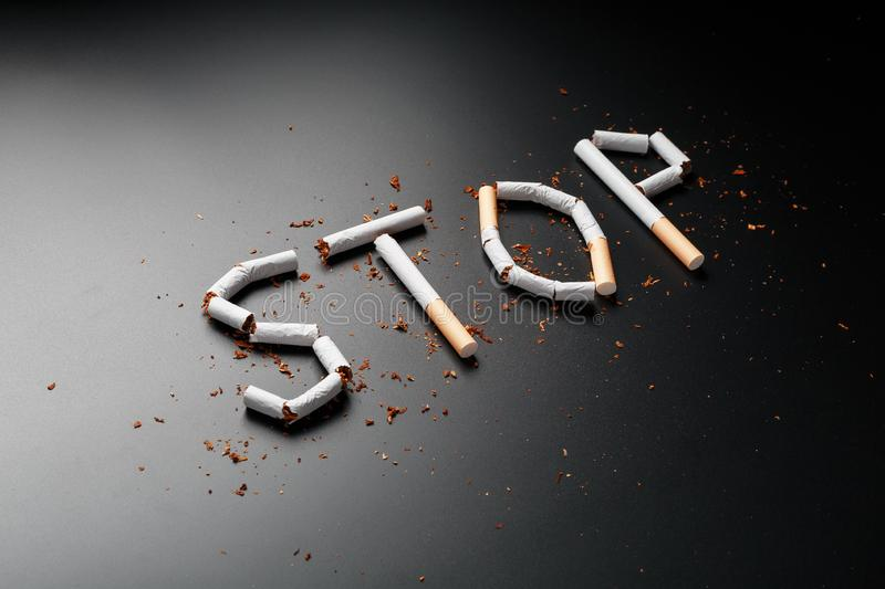 The inscription STOP from cigarettes on a black background. Stop smoking. The concept of smoking kills. Motivation inscription to. Quit smoking, unhealthy habit stock images