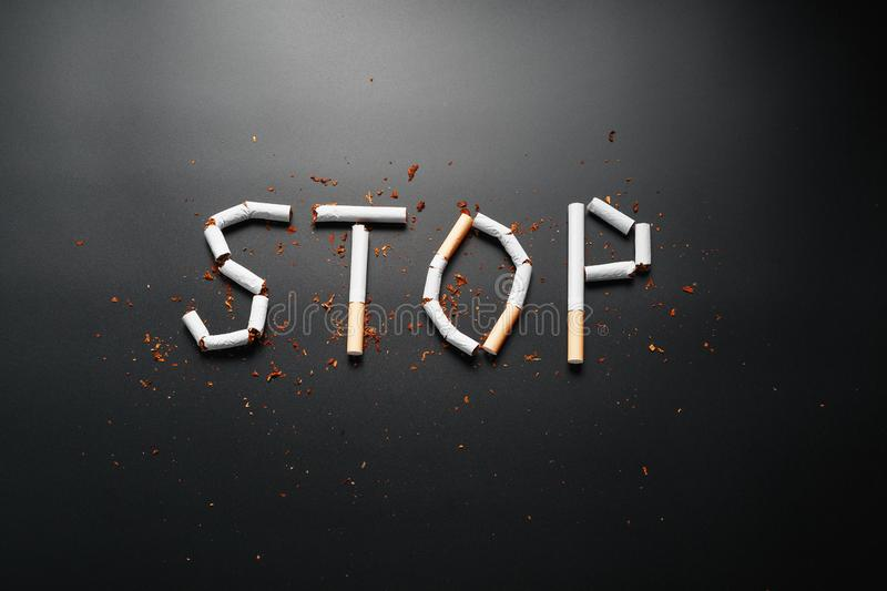 The inscription STOP from cigarettes on a black background. Stop smoking. The concept of smoking kills. Motivation inscription to. Quit smoking, unhealthy habit stock photography