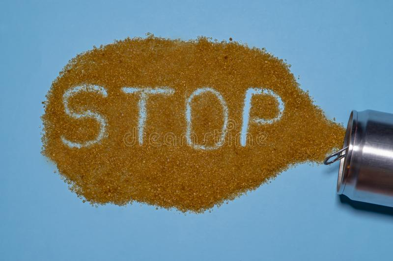 Inscription stop symbolizes call to limit immense consumption of sugar. Brown sugar, poured out of aluminum cans, symbolizes the stock photography