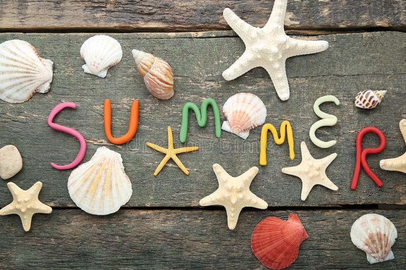 Inscription Summer. By plasticine with seashells on grey wooden table stock photos