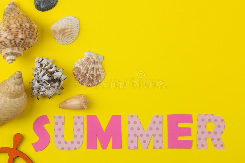 Inscription summer from paper of multi-colored letters and seashells on a bright yellow background. Summer. relaxation. vacation royalty free stock photography