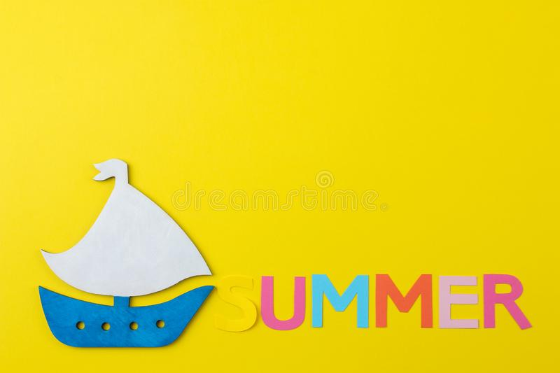 Inscription summer from paper of multi-colored letters and seashells and a ship on a bright yellow background. Summer. relaxation. Vacation stock image