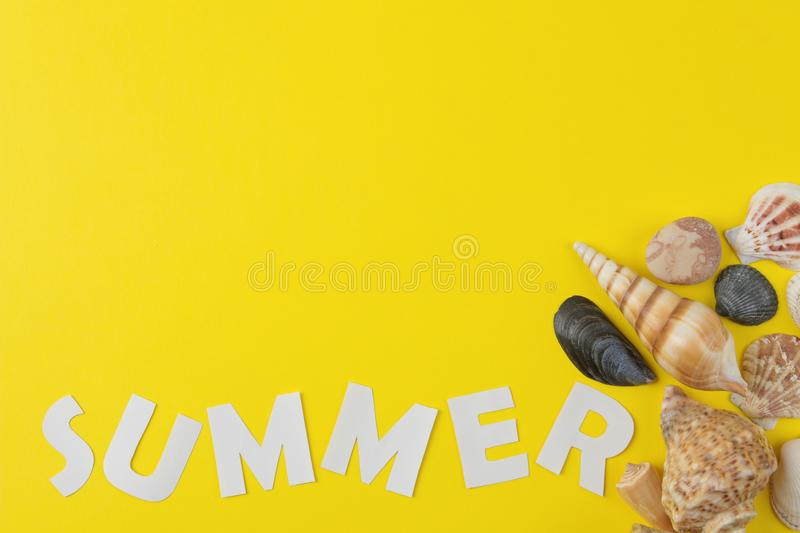 The inscription summer of paper white letters and seashells on a bright yellow background. Summer. relaxation. vacation. top view stock image