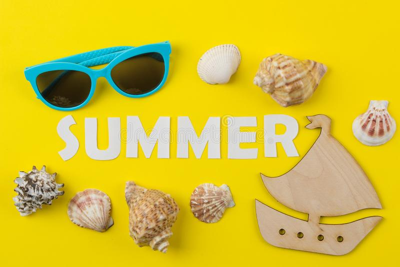 The inscription summer of paper white letters and seashells on a bright yellow background. Summer. relaxation. vacation. top view stock images