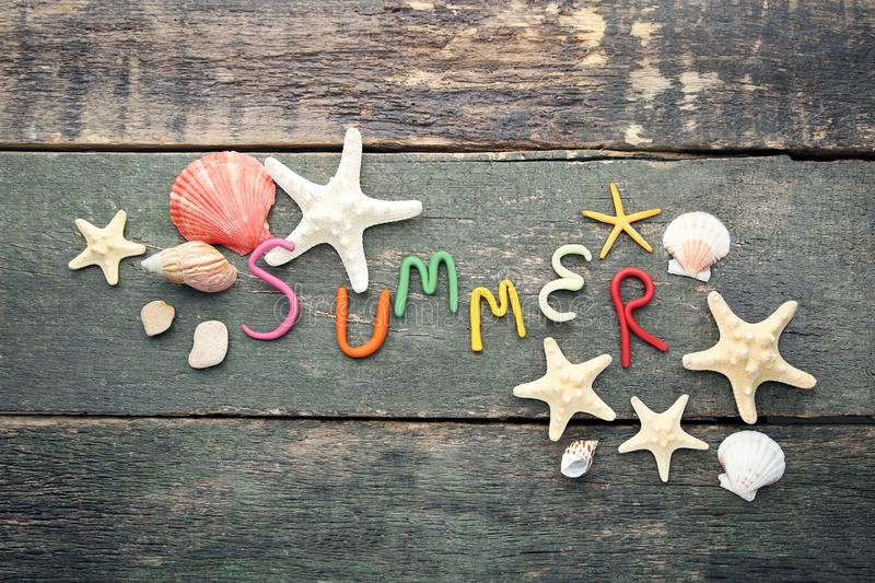 Inscription Summer. By plasticine with seashells on grey wooden table stock photo