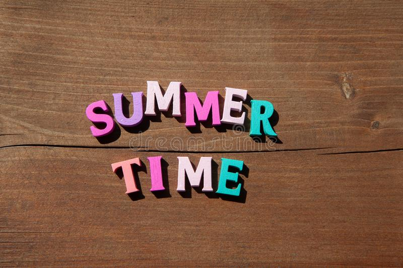 Inscription summertime by multicoloured wooden letters on wooden background. Concept happy summertime. Inscription summertime by multicoloured wooden letters on royalty free stock image