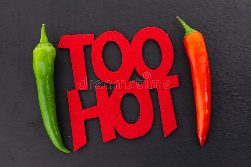 Inscription Too Hot hot chili pepper message poster parallel chili pod red green frame on black form bright message stock images