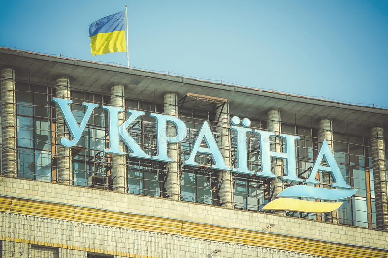 Inscription Ukraine on the building and the state flag of Ukraine. In the center of Kiev's Independence Square stock photos
