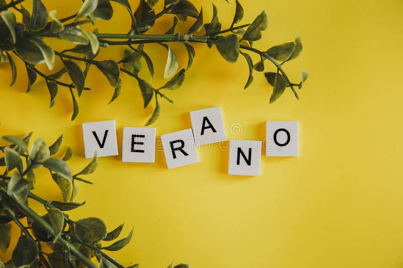 The inscription verano in spanish on the letters of the keyboard on a yellow background with branches of flowers royalty free stock images