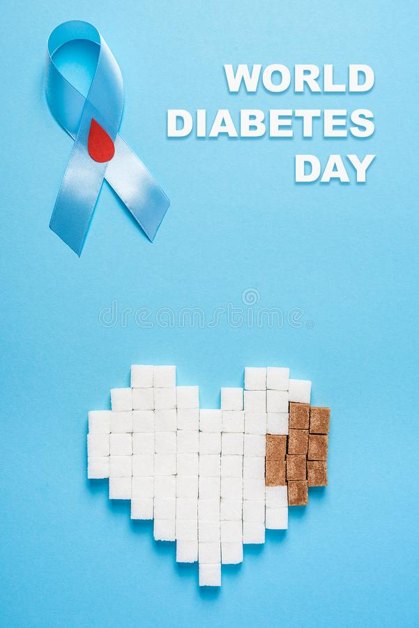 Inscription world diabetes day, blue ribbon awareness with red blood drop, broken heart of sugar cubes, blue background stock photography